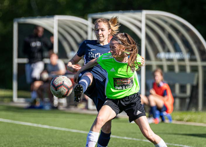 OAKVILLE, ON - JUN. 23, 2019: Players battle for the ball during a League1 Ontario women's soccer game between the Oakville Blue Devils and DeRo United.