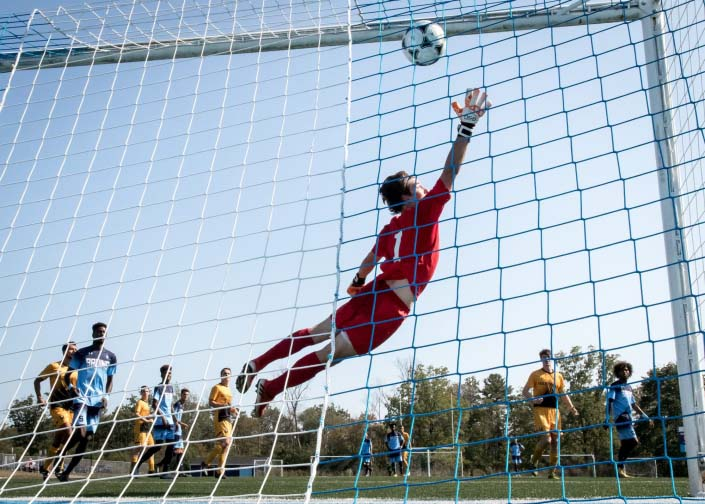 OAKVILLE, ON - SEP. 24, 2017: Dylan Roossien of the Cambrian Golden Shield fails to stop a free kick from Emilio Estevez of the Sheridan Bruins.