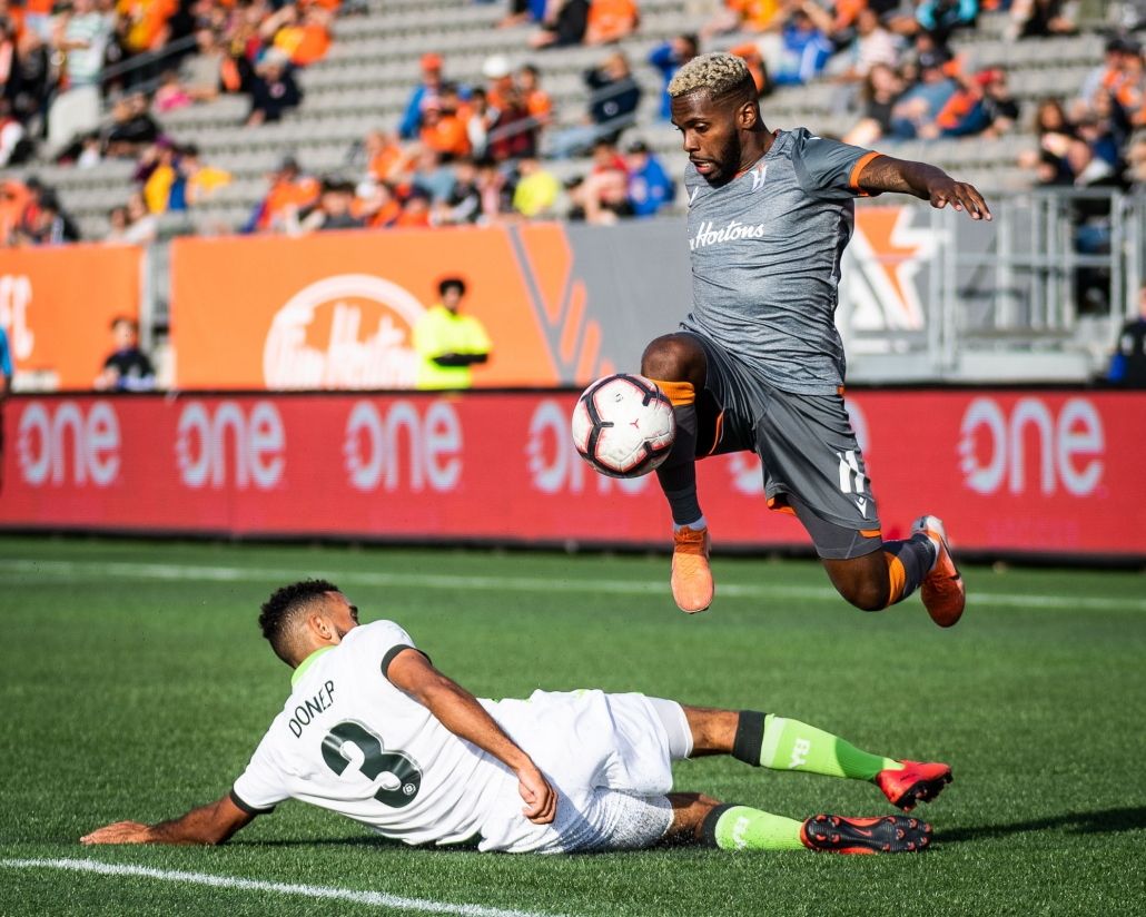 HAMILTON, ON - OCT. 6, 2019: Christopher Nanco of Forge FC jumps over Morey Doner of York9 FC in Canadian Premier League action.