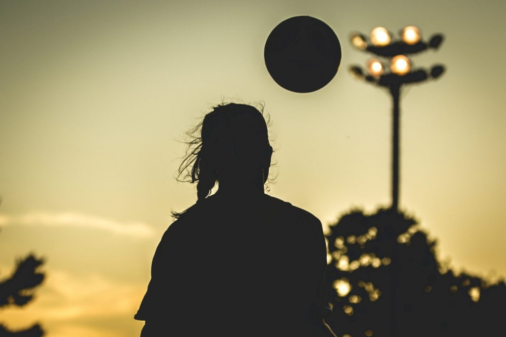 OAKVILLE, ON - AUG. 15, 2016: A silhouetted player brings down the ball under a golden sunset.