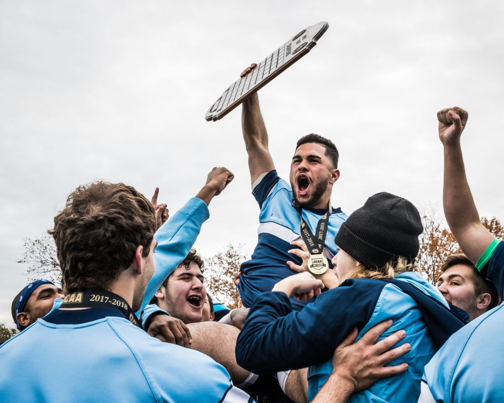OAKVILLE, ON - NOV. 12, 2017: Jad Hamade of the Sheridan Bruins hoists the OCAA Men's Rugby Championship plaque into the air after a victory against the St. Lawrence Vikings.