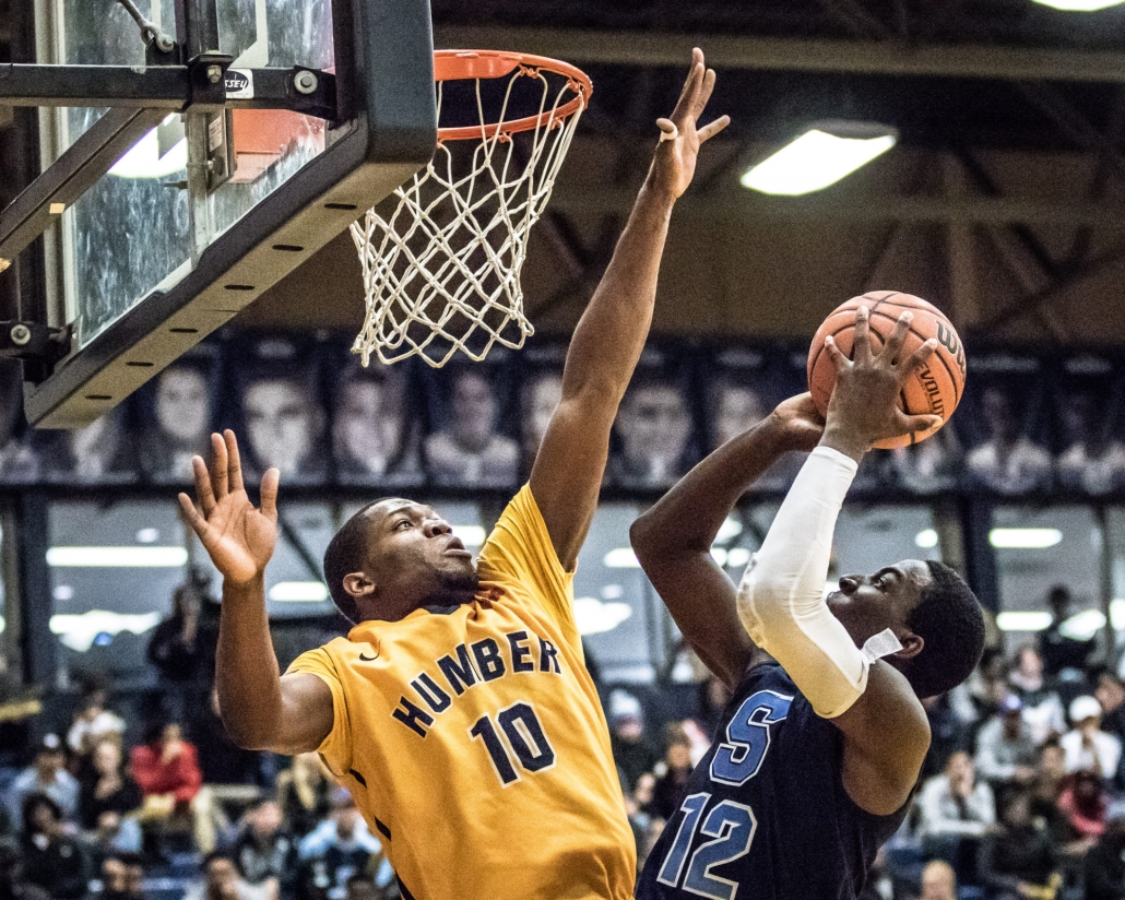 TORONTO, ON - NOV. 12, 2016: Tremaine Hibbert of the Sheridan Bruins tries to release a short jumper against Tyrone Dickson of the Humber Hawks.