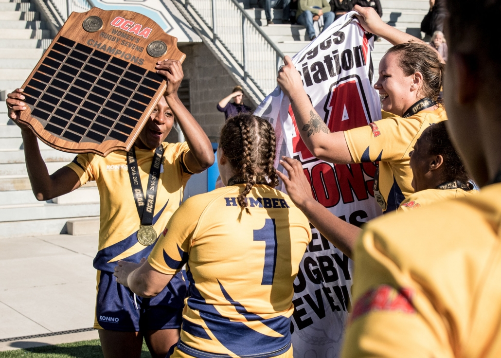 OAKVILLE, ON - Nov. 5, 2016: Christina Branch is surrounded by her Humber teammates as they celebrate winning the inaugural OCAA Women's Rugby Sevens Championship.