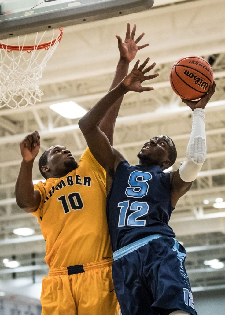 TORONTO, ON – Mar. 3, 2017: Tremaine Hibbert of the Sheridan Bruins battles under the hoop against Tyrone Dickson of the Humber Hawks.